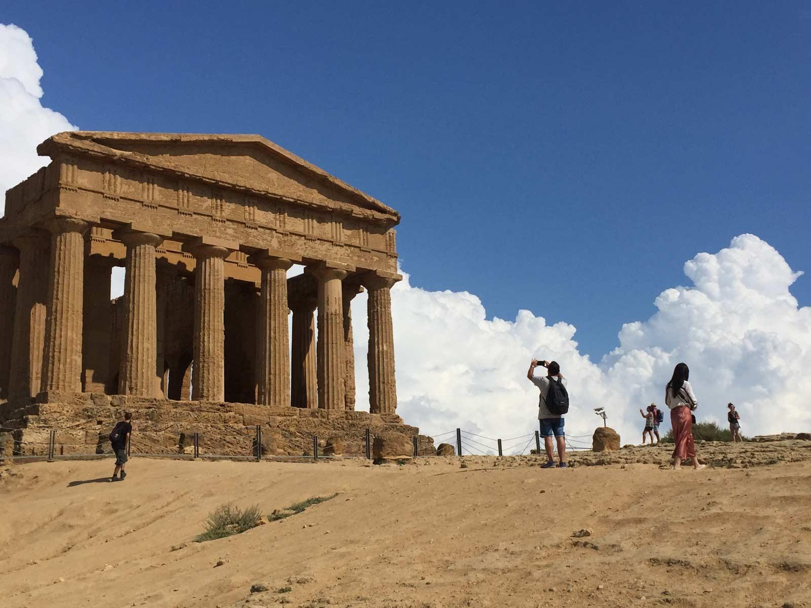 Tempio-della-Concordia-Agrigento con le nuvole sullo sfondo e alcuni visitatori che scattano foto