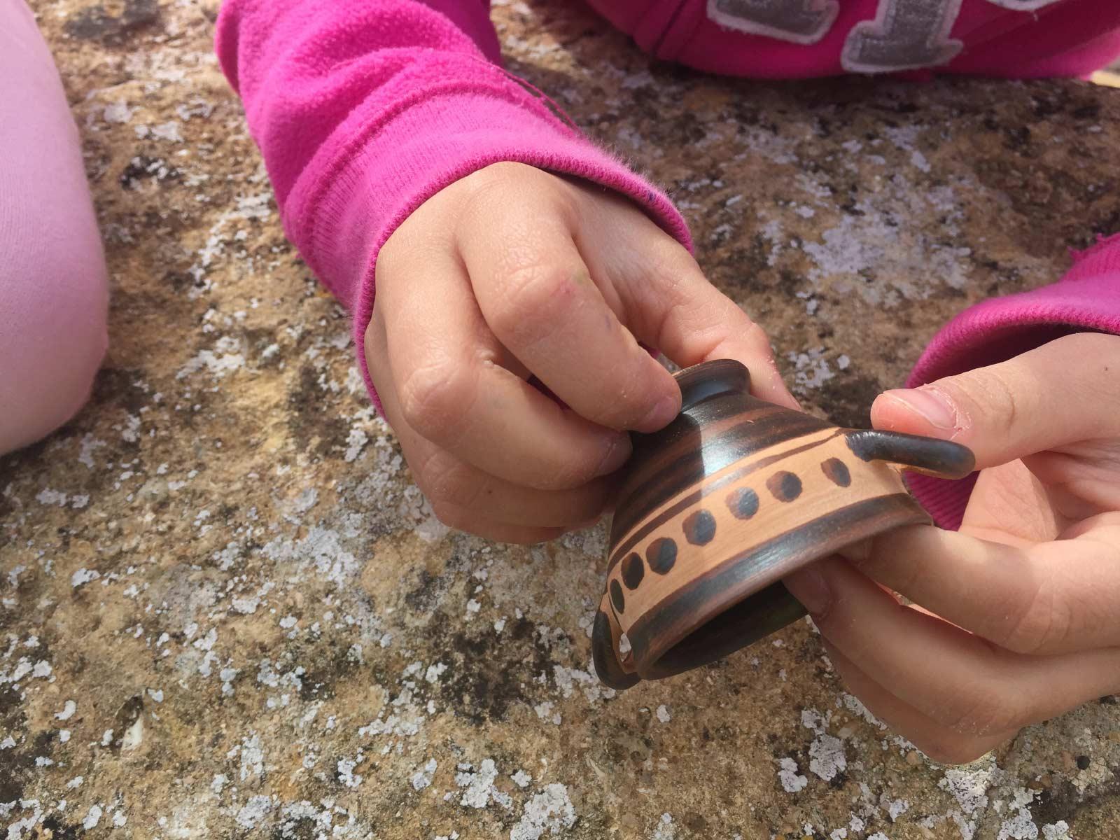 Una bimba usa il tatto per conoscere un reperto archeologico: una piccola coppetta (skyphos) a vernice nera decorata con una fila di puntini