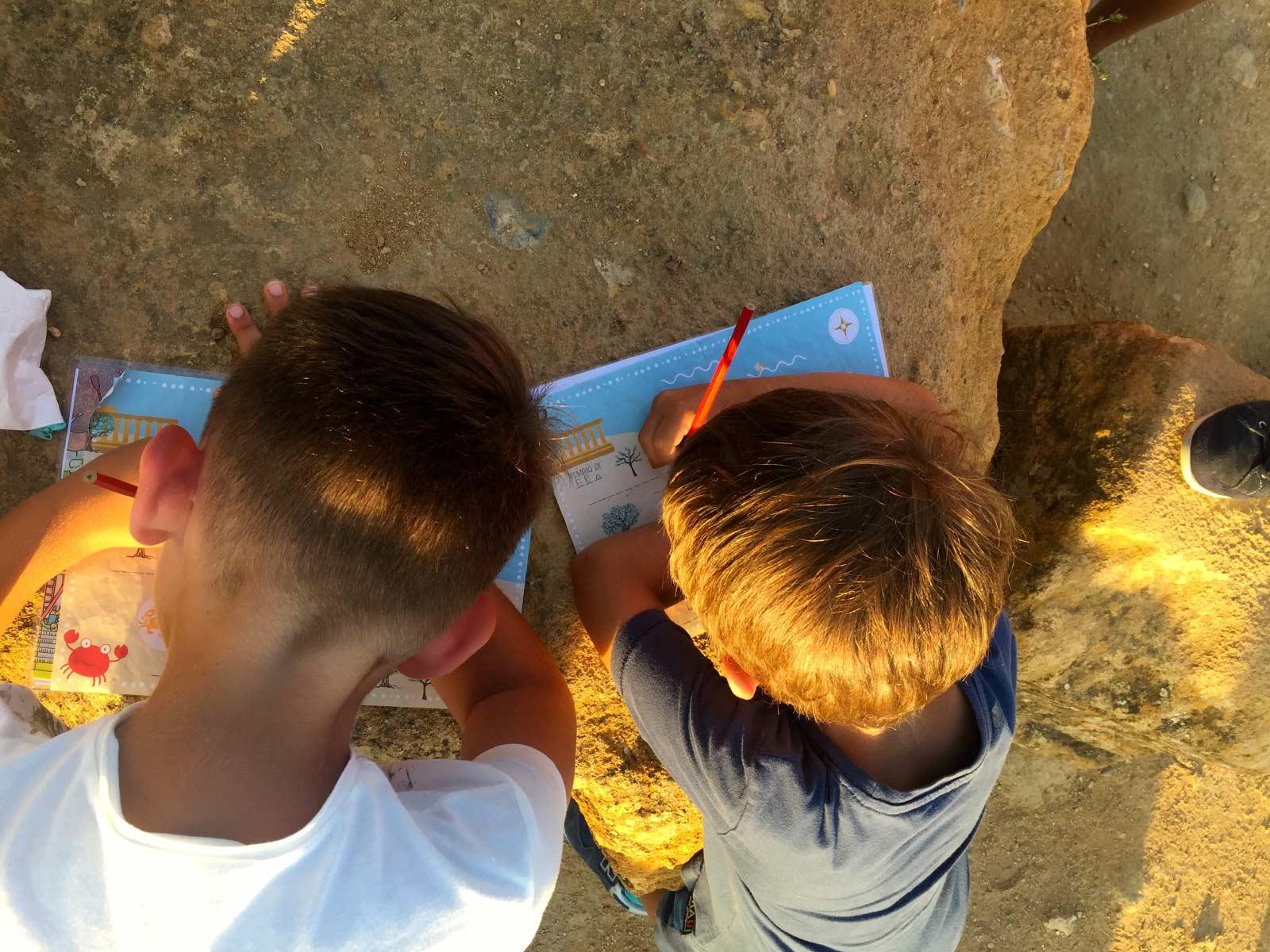 Due bambini compilano la mappa a colori della valle dei templi for kids appoggiati a un blocco di arenaria durante un family tour alla valle dei templi al tramonto in estate
