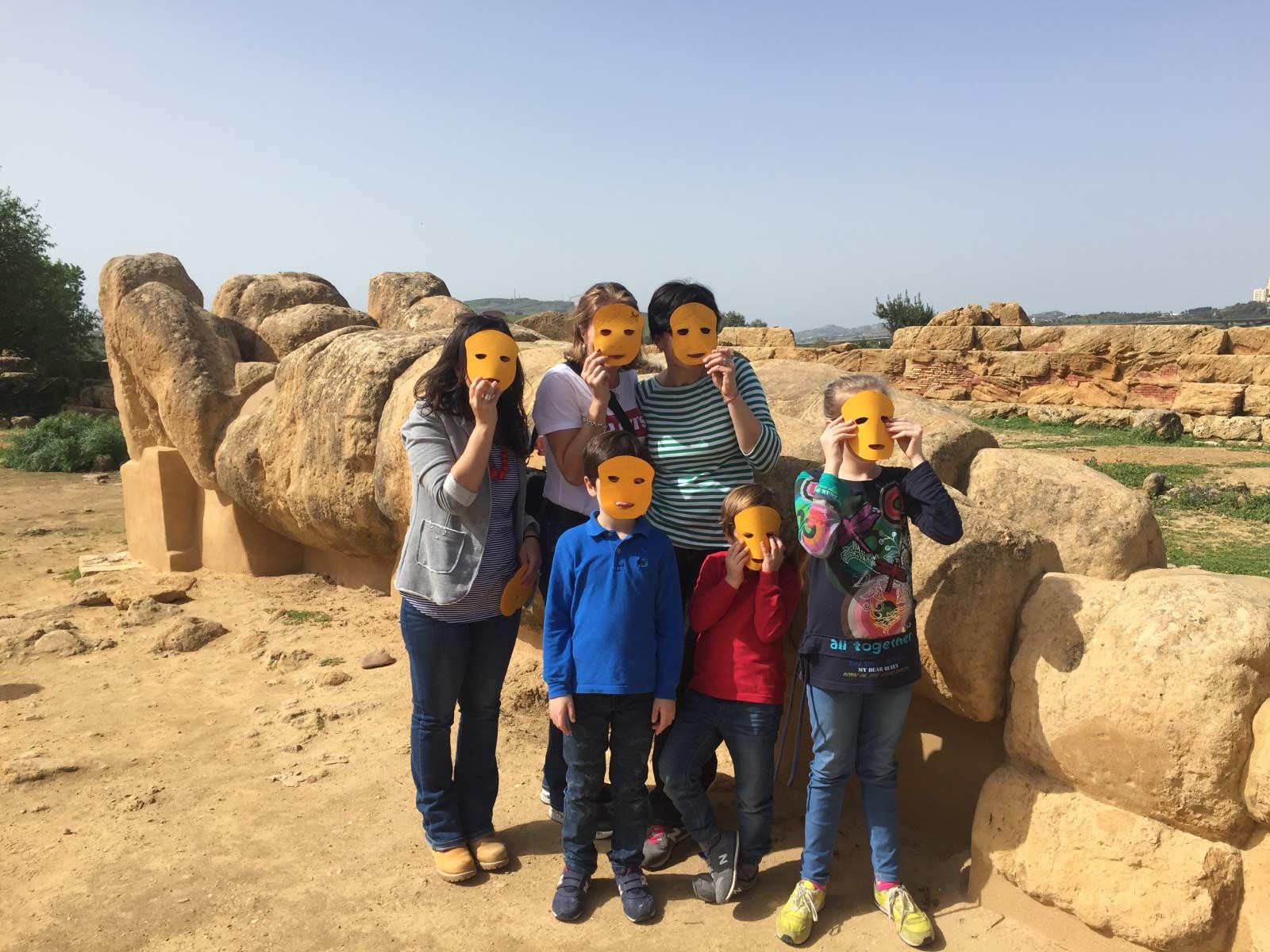 Foto di gruppo con la guida davanti al Telamone del tempio di Zeus al parco valle dei templi con una famiglia con tre bambini e due adulti che indossano le maschere per somigliare al telamone
