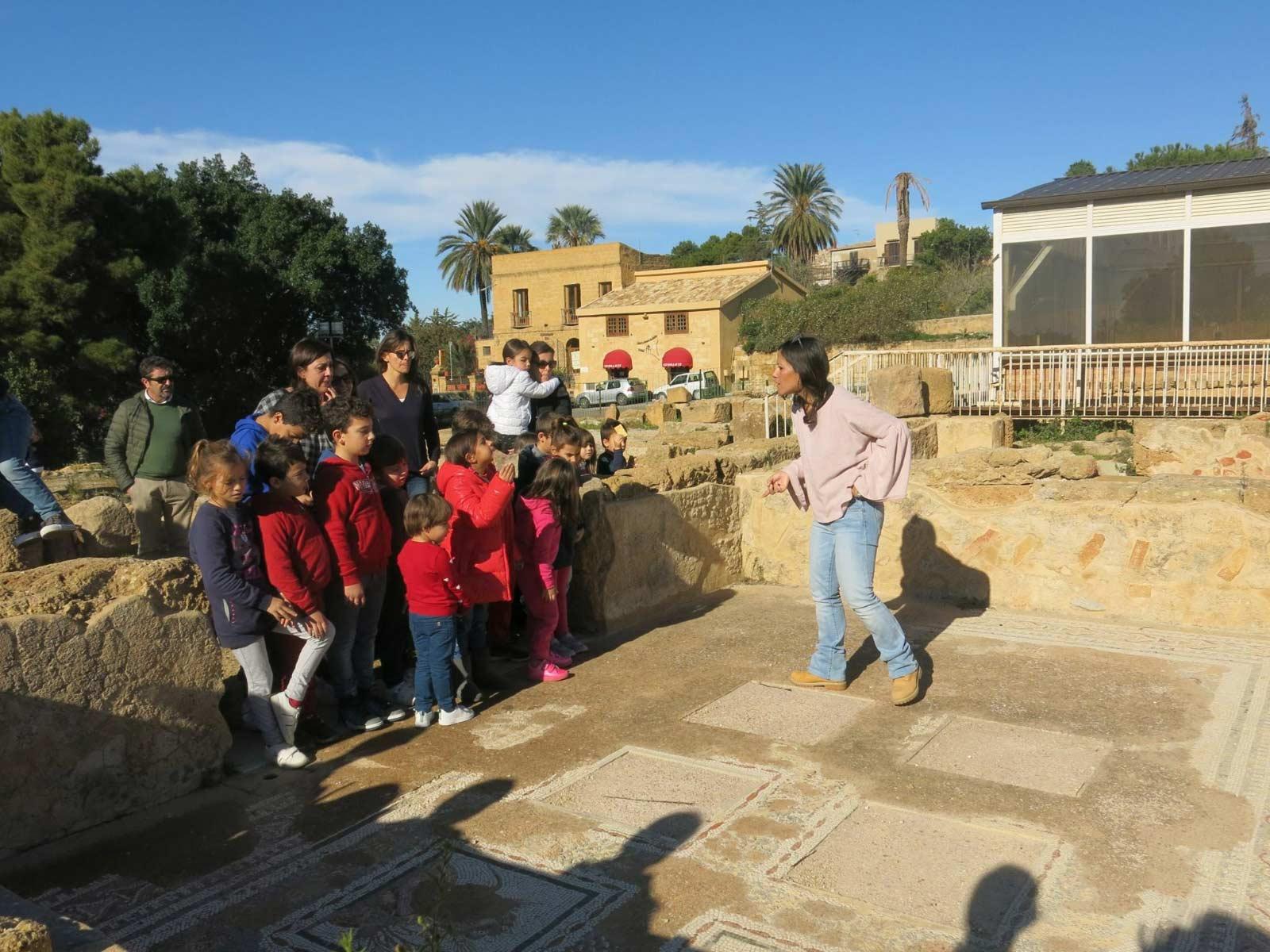 La guida Laura Danile descrive uno dei mosaici che decorano le case degli antichi a un gruppo di famiglie con bambini