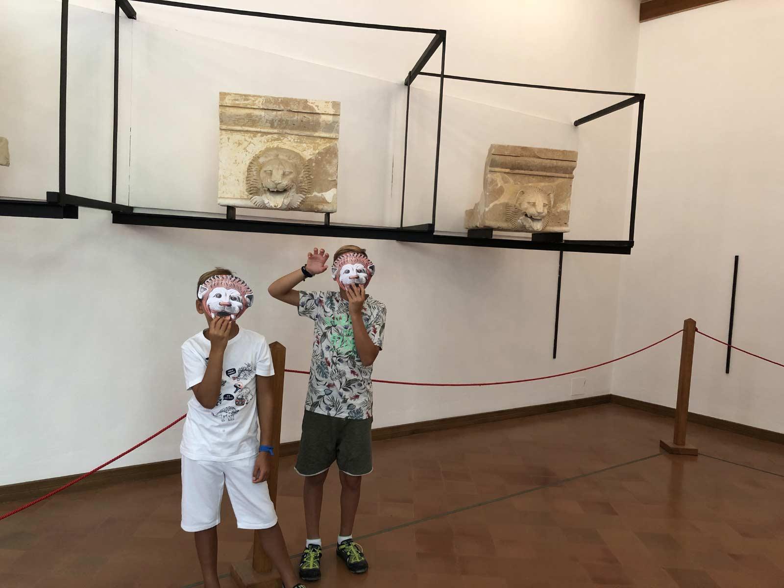 Due bambini posano con maschere di leone davanti ai reperti di gronde leonine del museo archeologico di Agrigento