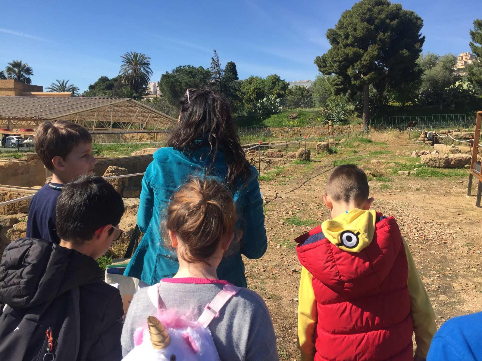 La guida Laura Danile cammina lungo una delle strade del quartiere ellenistico romano con un gruppo di bambini durante un family tour
