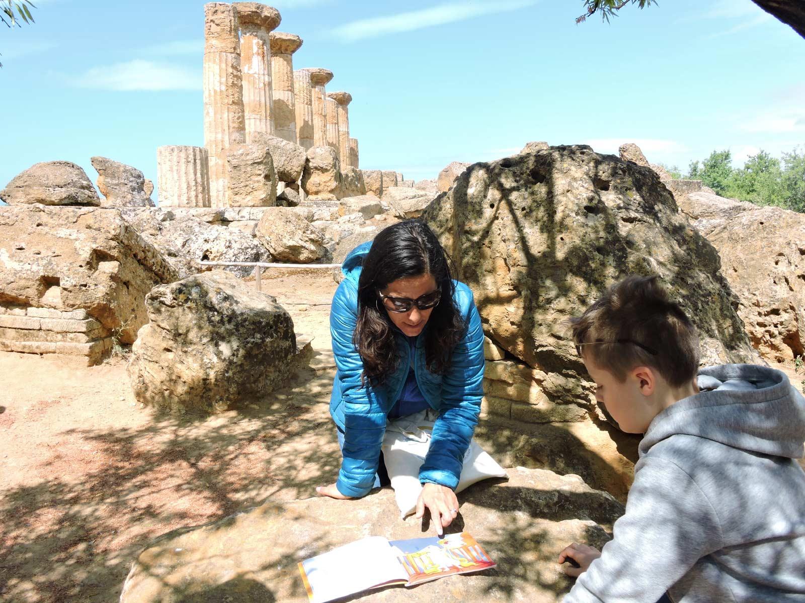 La guida Laura Danile con un libro illustrato racconta le fatiche di Ercole a un bambino davanti al tempio di Ercole nella Valle dei Templi