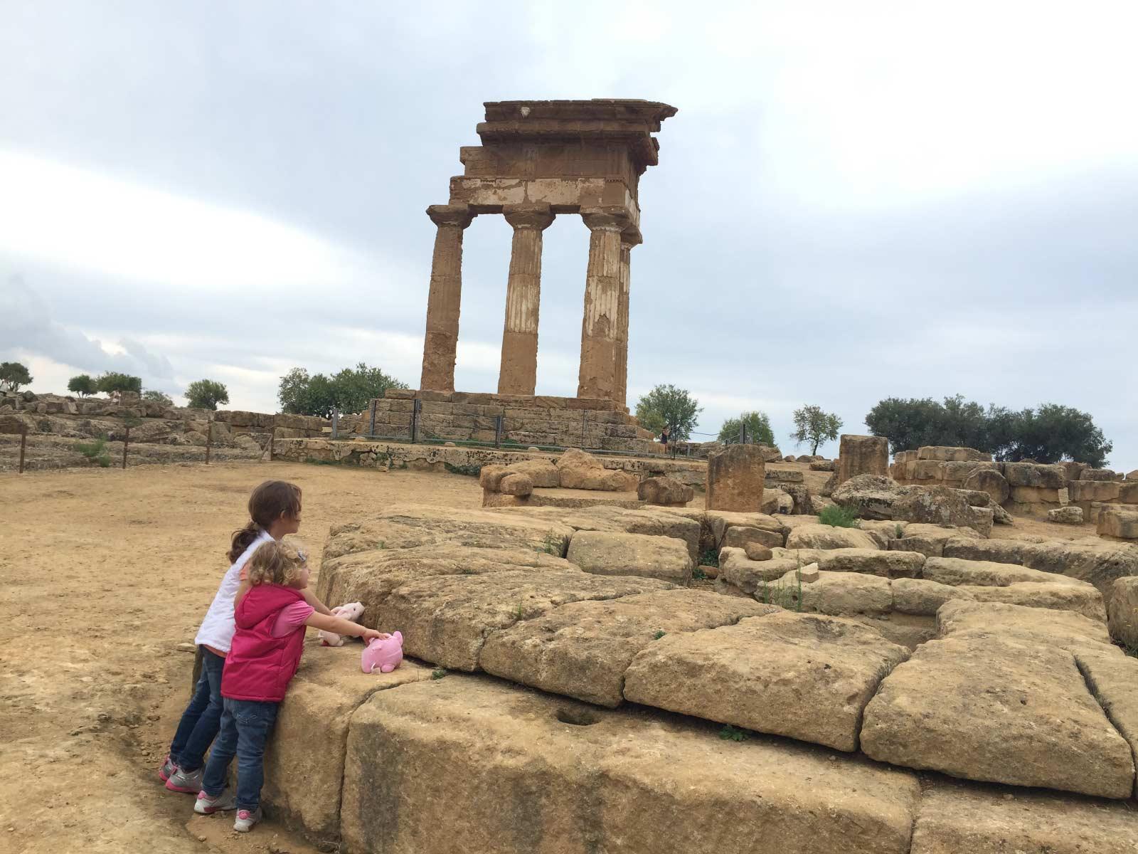 Due bambine offrono i maialini di peluche sull'altare circolare di Demetra con il tempio dei Dioscuri sullo sfondo