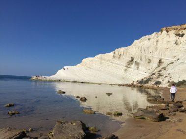 La scala dei turchi che si specchia sull'acqua del mare e una persona che passeggia in spiaggia
