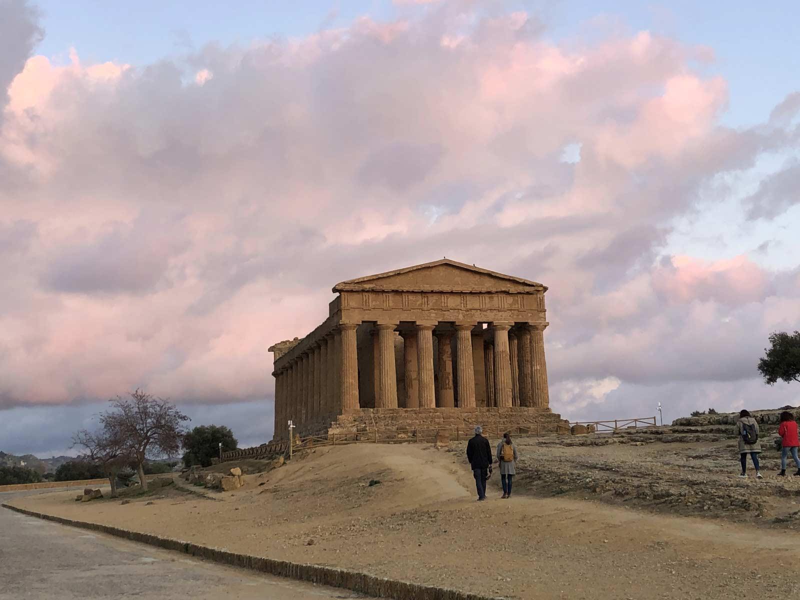 Tempio della Concordia al tramonto con una coppia di visitatori davanti e le nuvole rosa dietro