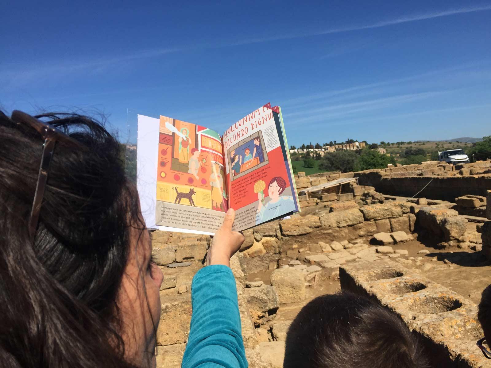 La guida Laura Danile con un libro illustrato a colori racconta il termopolium ai bambini durante un family tour