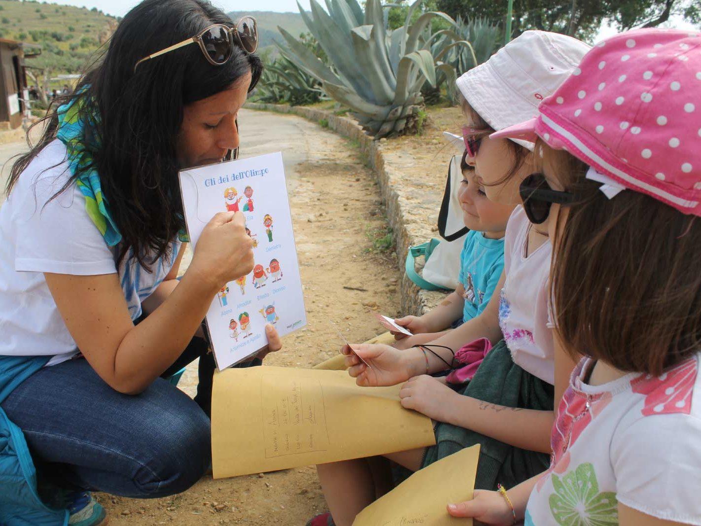 La guida Laura Danile presenta gli dei greci ai bambini utilizzando una immagine a colori durante un family tour