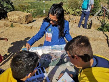 Laura Danile illustra la ricostruzione della collina dei templi a colori a due ragazzi durante un family tour