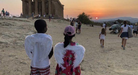 Tempio della Concordia al tramonto con due bambini che indossano le ali di icaro mentre ne guardano la statua di bronzo