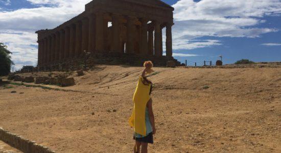 Una bambina davanti al tempio della Concordia con indosso il mantello di Ercole (leontè) e in mano il peluche di un leoncino