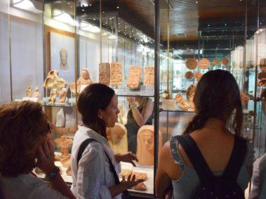 Laura Danile con una famiglia davanti alla vetrina con i reperti di terracotta dal santuario ctonio al Museo Archeologico di Agrigento