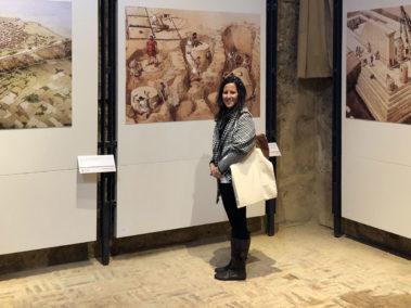Laura Danile davanti a pannelli a colori che rappresentano la costruzione dei templi al Museo Archeologico