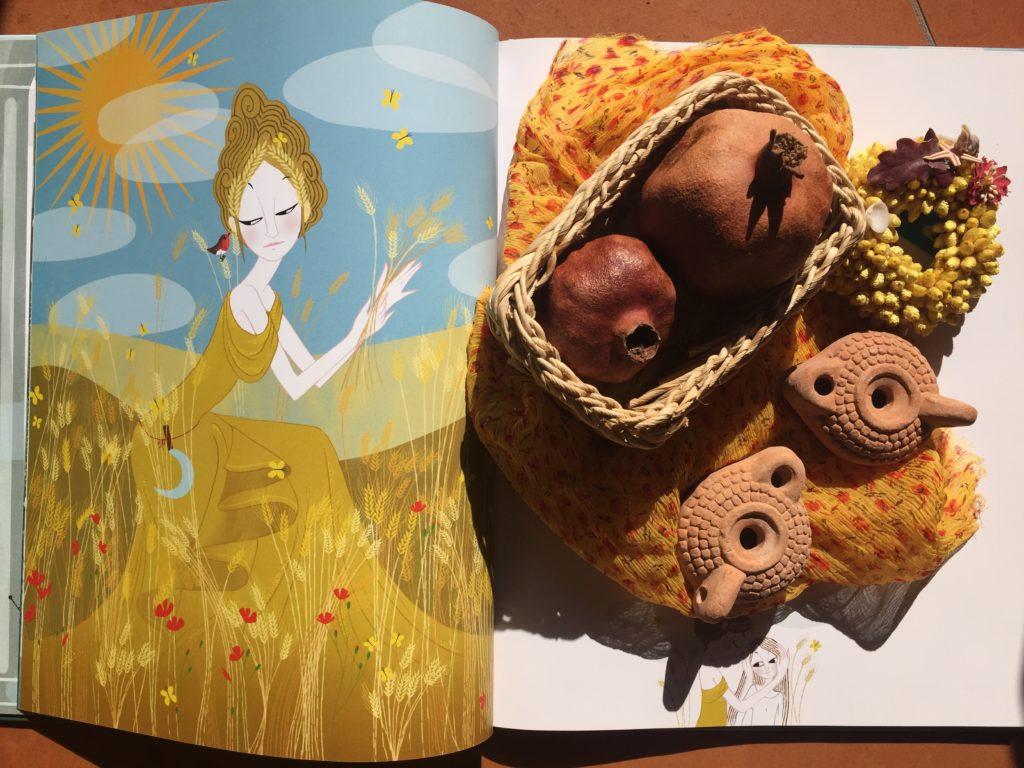 Libro di mitologia illustrato per bambini e oggetti legati al mito di Demetra: melograni, lucerne, fiori