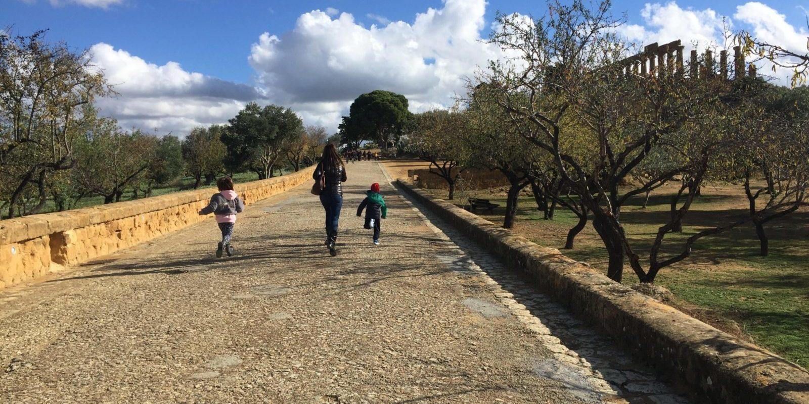 Mamma e due bambini che corrono lungo la via sacra tra mandorli e ulivi verso il tempio di Giunone sullo sfondo sotto un cielo azzurro con nuvole bianche